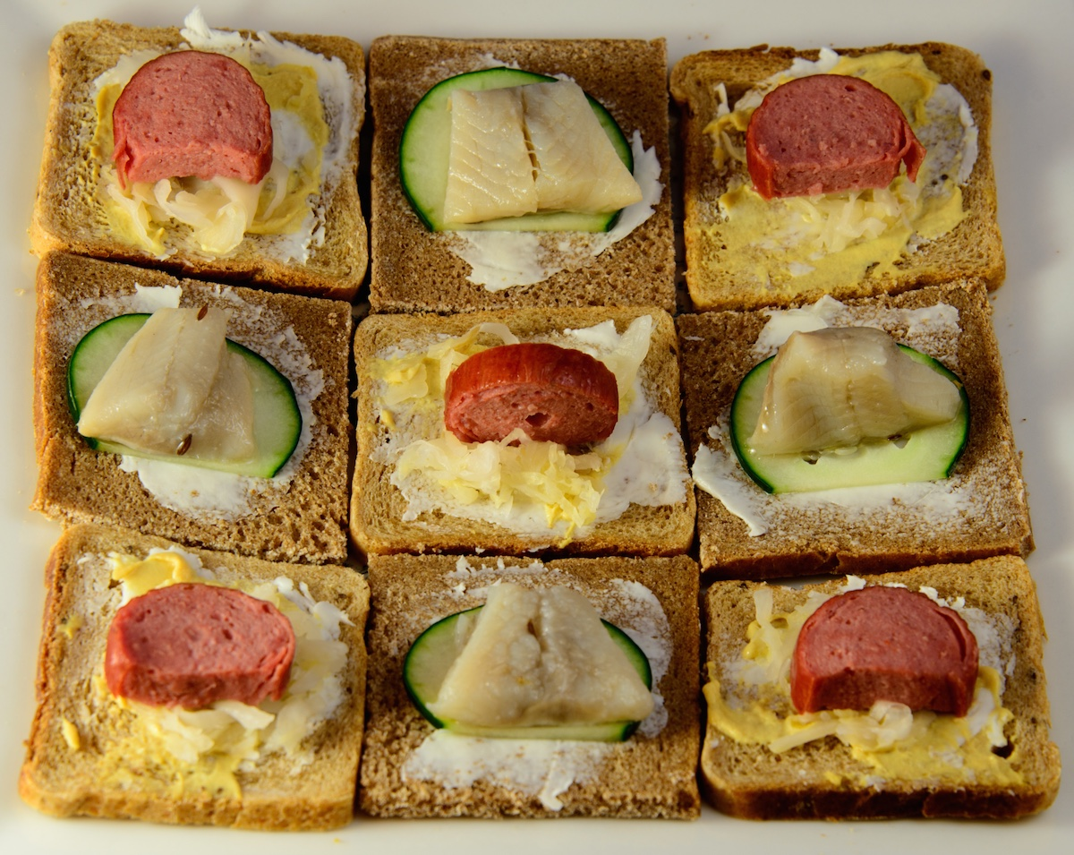 A plate of open face Danish-style sandwiches, as seen from above, arranged in a checkerboard pattern. The sausages are cut into half-round coins, and the herring is cut into trapezoids.