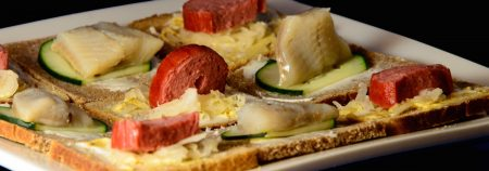 "A plate of open-face Danish-style sandwiches, ""Tak Snacks"" as seen from the side so you can see the sausage and herring standing up like standing stones on the Tak board."