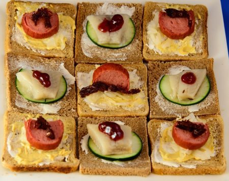 A plate of open face Danish-style sandwiches, as seen from above, arranged in a checkerboard pattern. This time garnishes (lingonberry jam and sundried tomato) are visible