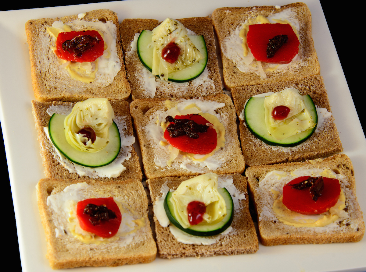 A plate of open face Danish-style sandwiches, as seen from above, arranged in a checkerboard pattern. These are the vegetarian sandwiches, featuring roasted red bell pepper cut into half round shapes, and pickled artichoke hearts cut into trapezoids.
